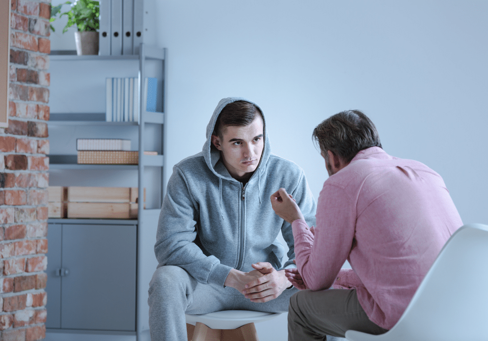 Young male sitting with older male therapist