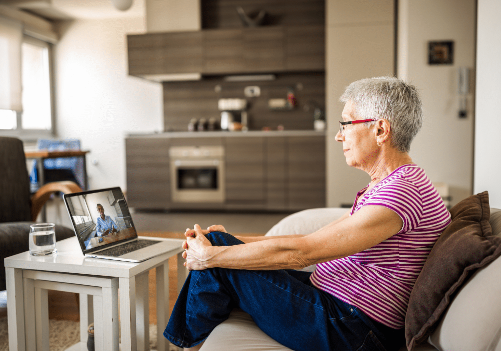 Older woman sits in front of laptop with online therapist